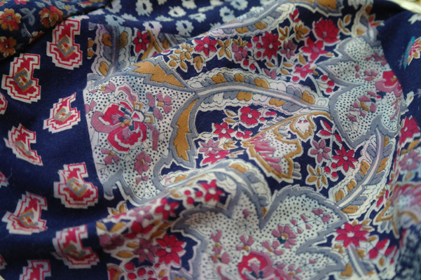 The patterned blue and purple fabric of a vintage bag.
