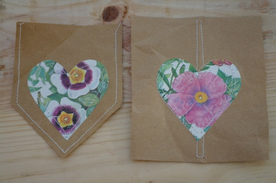 Individual paper heart bunting flags. Glued down, and stitched onto paper bag.