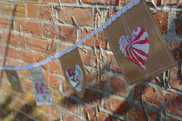 Heart bunting, made with recycled paper (old sheet music, paper bags, old flower illustrations), and lace.