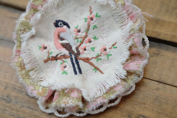 Close up of finished embroidered bird brooch. Upcycled, recycled, repurposed. Textile jewellery. Fabric brooch.