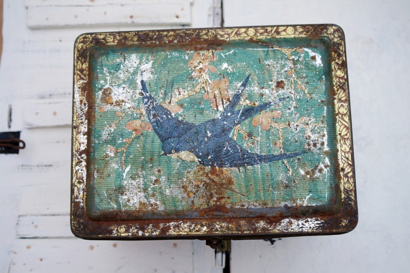 Vintage tin decorated with bluebird. Scratched and rusty.