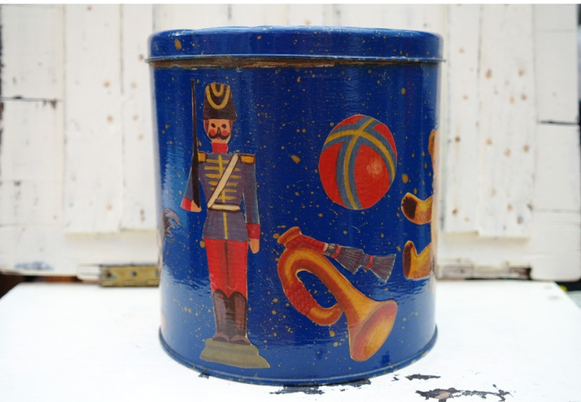 Vintage tin, with nutcracker style decorations.