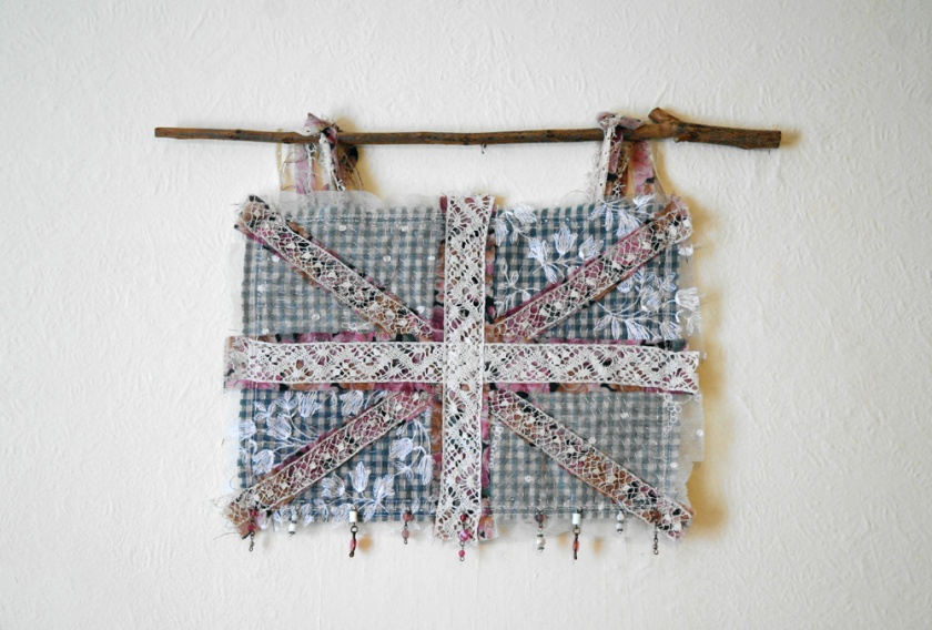 Union Jack textile wall hanging. Made with vintage lace, plaid fabric, and lots of beads. Beaded lace wall hanging.