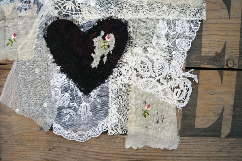 Wall hanging work in progress. Made with vintage lace, vintage plaid fabric, and antique rose embroidery pieces. Black lace heart.