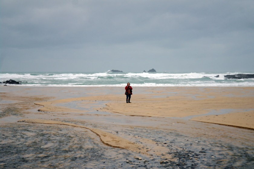 Mama Pippin in the distance. Person on beach. Winter coast. Cornish seaside in January. Grey sky and rough sea.