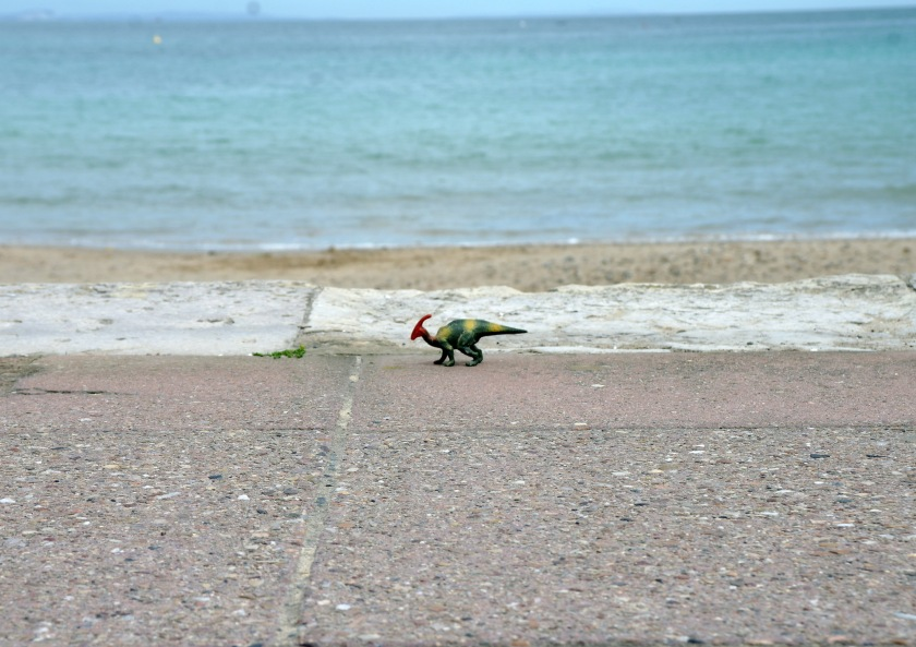 Toy dinosaur on the promenade in Swanage, Dorset. Jurassic coast. Seaside finds. Beachcombing finds.