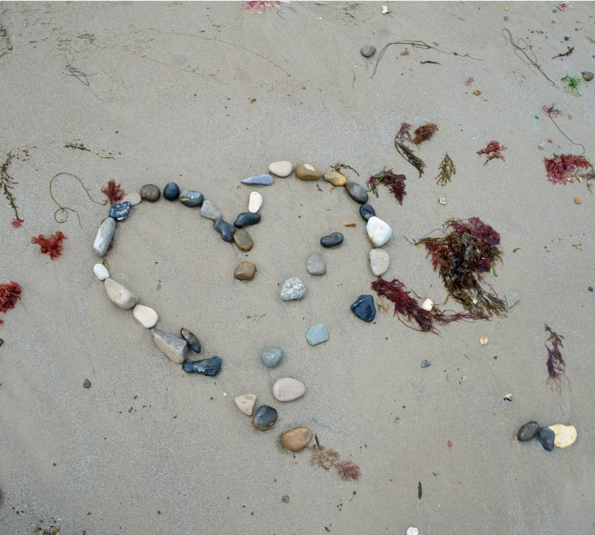 Partially washed away heart made of pebbles on the beach at Swanage, Dorset. Beach art. Stone and pebble heart.