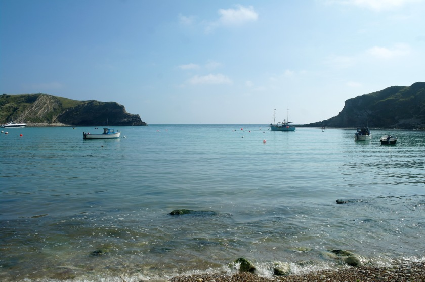 Looking out across Lulworth Cove, Dorset, England. Boats in Lulworth Cove on a sunny September day.